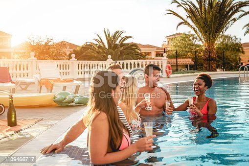 istock Group of happy friends making a pool party at sunset - Millennial young people laughing and having fun drinking champagne in the pool - Friendship, holidays and summer youth lifestyle concept 1139466717