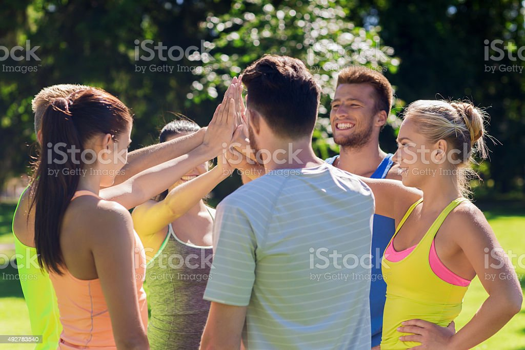 group of happy friends making high five outdoors stock photo