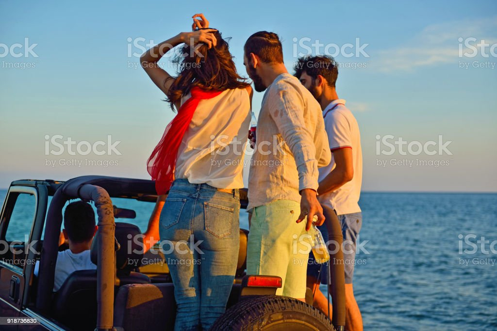 Group of happy friends making party in car - Young people having fun drinking champagne stock photo