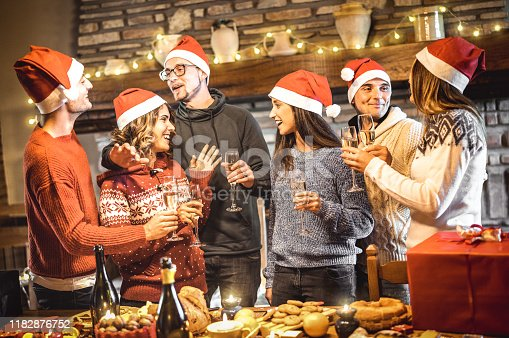 Group of happy friends on santa hats celebrating Christmas with wine and sweet food at dinner party - Winter holiday concept with young people sharing time having fun and eating together - Warm filter