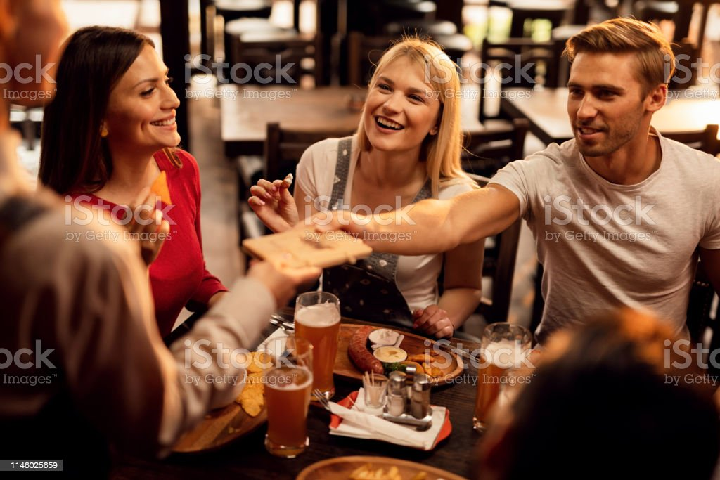 Young happy friends enjoying in lunch in tavern and paying bill to a...