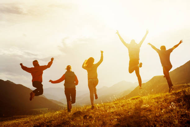 Group of happy friends run and jump Group of five happy friends is running and jumping in sunset light on background of mountains. Happiness and friendship concept mid air stock pictures, royalty-free photos & images