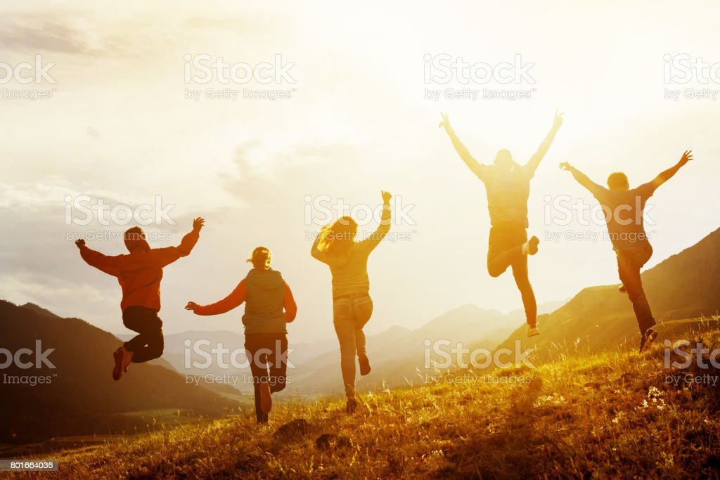 Group of happy friends run and jump stock photo