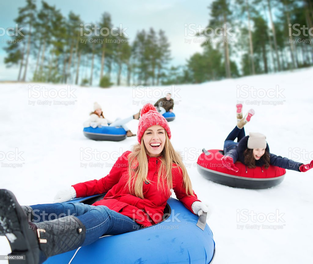 group of happy friends sliding down on snow tubes stock photo