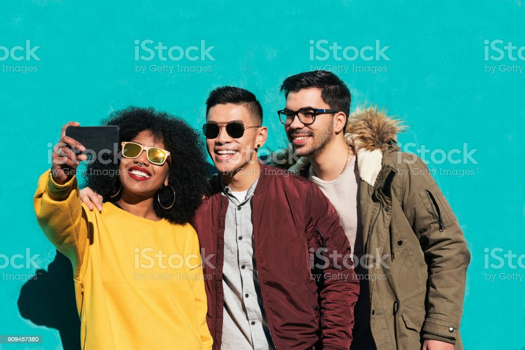 Group of happy friends taking a selfie in the street. stock photo