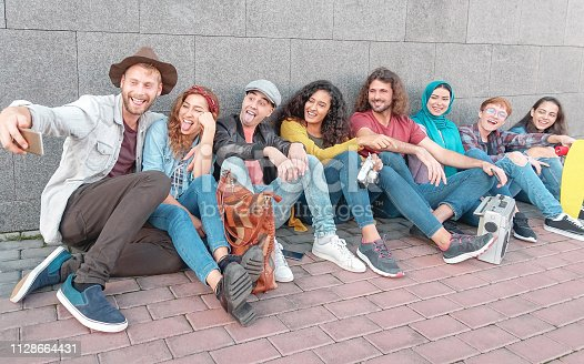 istock Group of happy friends taking selfie with mobile smart phone camera - Millennial young people having fun making photos for new social network trends - Multiracial, technology, youth lifestyle concept 1128664431