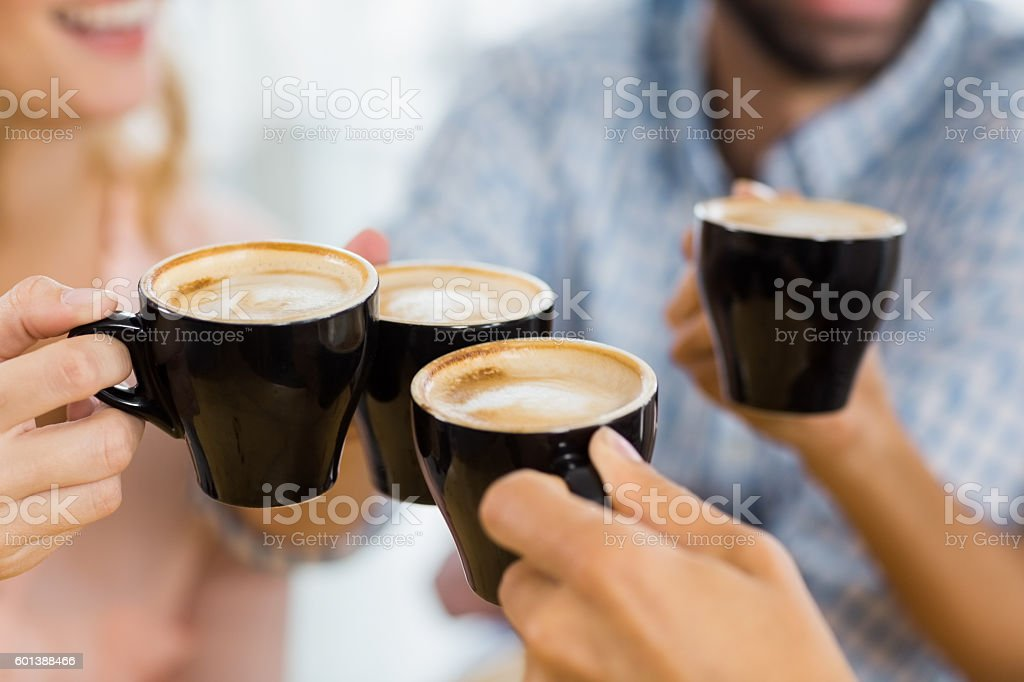 Group of happy friends toasting cup of coffee stock photo