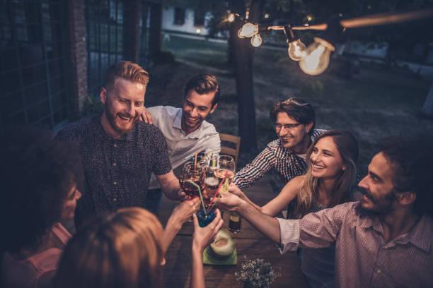 Grupo de amigos felizes torrar em uma noite de festa no quintal. - foto de acervo