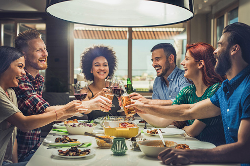Young cheerful people having fun at dinner party and toasting with alcohol.
