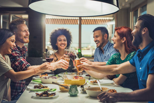 Group of happy friends toasting while eating at dining table. stock photo