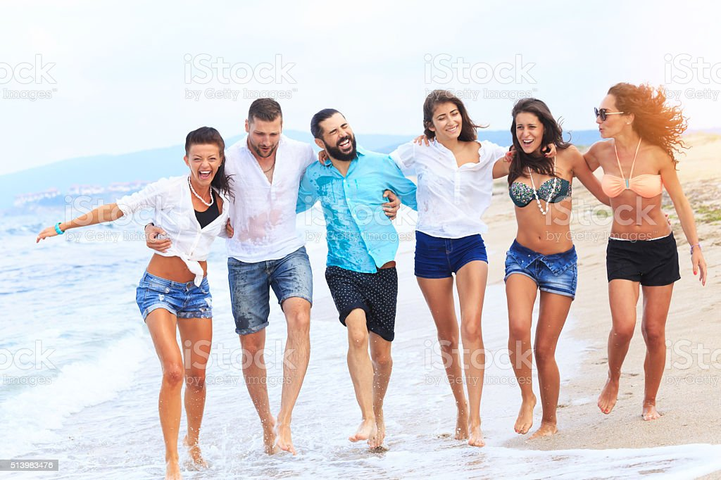 group of happy friends walking among the waves stock photo more