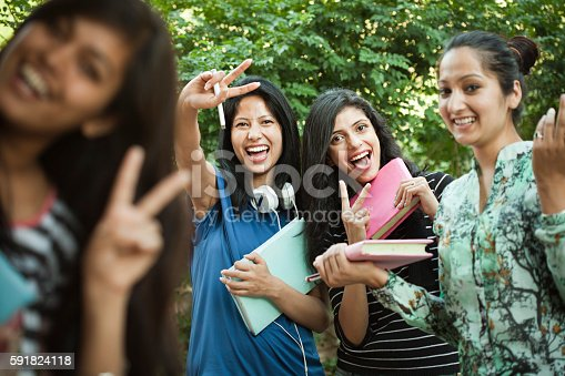istock Group of Happy girl students showing peace hand sign. 591824118