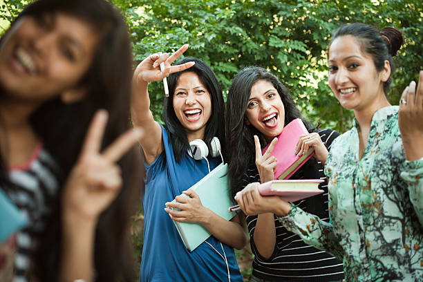 Group of Happy girl students showing peace hand sign. stock photo