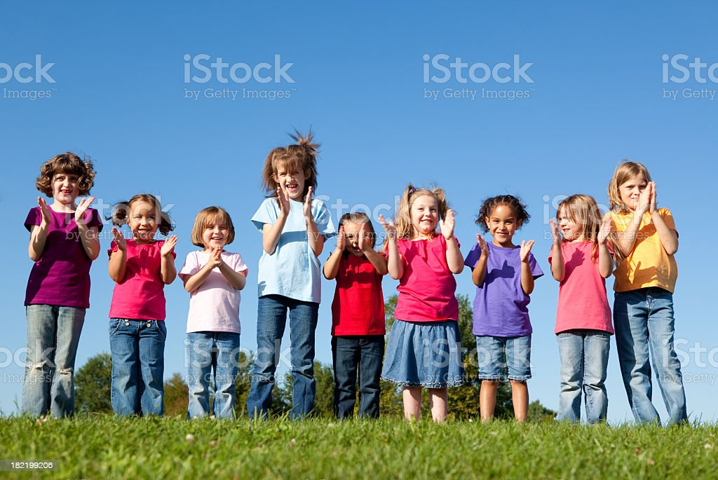 Group of Happy Girls Cheering and Clapping Color photo of a group of nine happy girls in a row clapping and cheering together outside on a beautiful summer day with a blue sky in the background. 4-5 Years Stock Photo