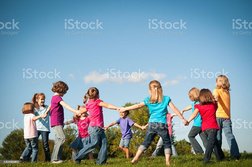Groupe heureux jeunes filles tenant les mains dans un cercle extérieur - Photo