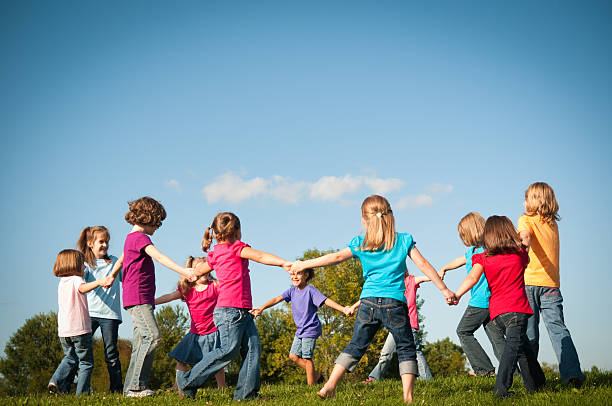 Group of Happy Girls Holding Hands in Circle Outside stock photo