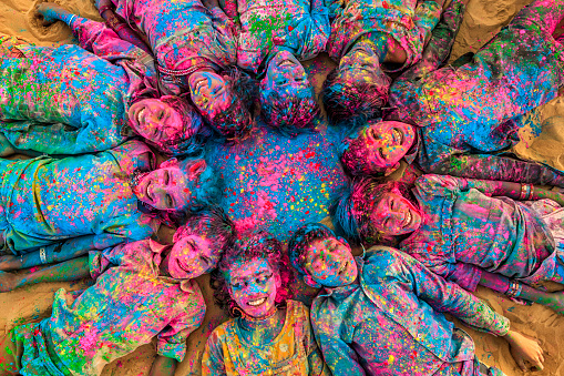 Group of happy Gypsy Indian children playing happy holi on sand dunes in desert village, Thar Desert, Rajasthan, India. Children are lying in a circle. Color powders are on their faces and clothes. Holi is a religious festival in India, celebrated, with the color powders, during the spring.