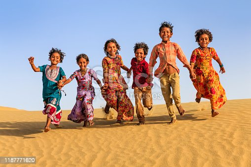 Group of happy Indian children running across sand dune - desert village, Thar Desert, Rajasthan, India.