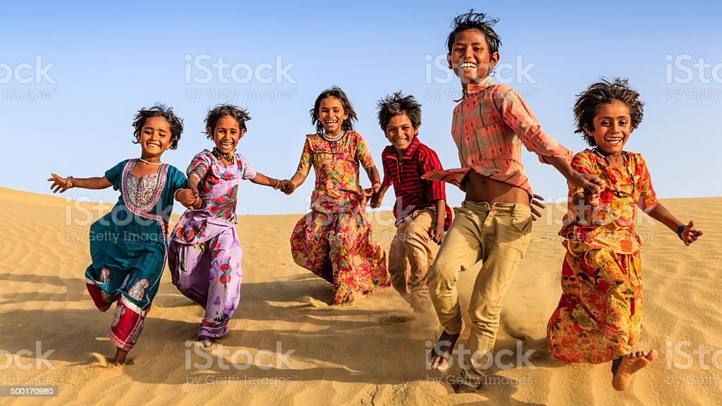 Group of happy Indian children running across sand dune, India stock photo