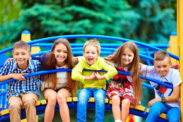 gruppe von glücklichen kindern mit spaß auf dem spielplatz - kinderspielplatz stock-fotos und bilder