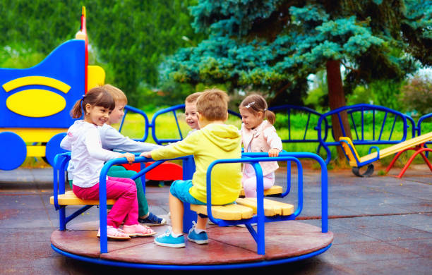 group of happy kids having fun on roundabout at playground stock photo