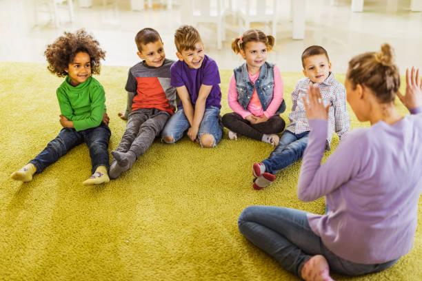 gruppe von glückliche kinder spaß mit ihrem lehrer an der vorschule. - erzieherin stock-fotos und bilder
