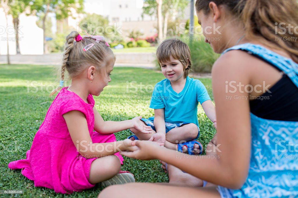 Group of happy kids playing on the grass. stock photo
