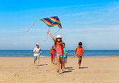 istock Group of happy kids run with kite on the beach 1210697813