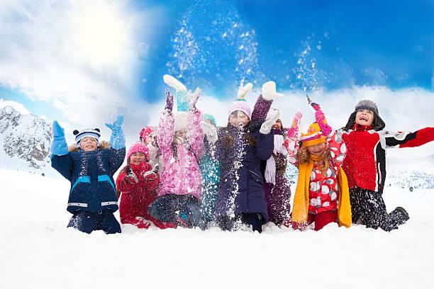gruppe von glücklichen kindern werfen schnee - schneespiele stock-fotos und bilder