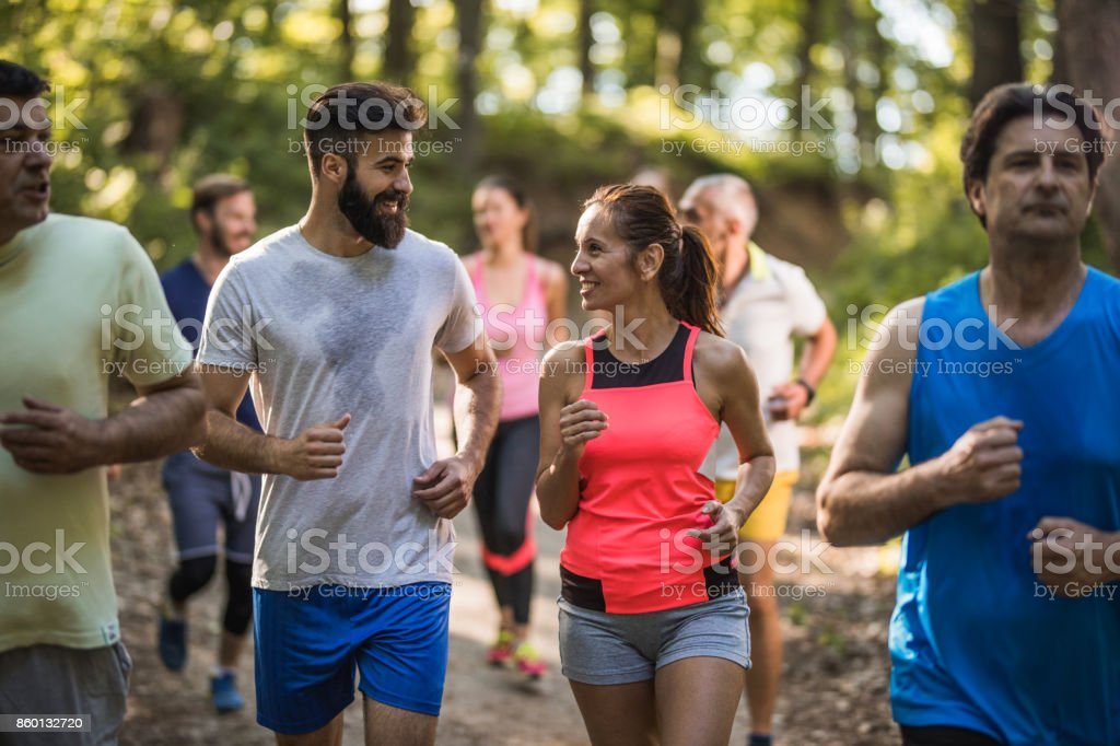 Group of happy marathon runners communicating during a race through nature. stock photo