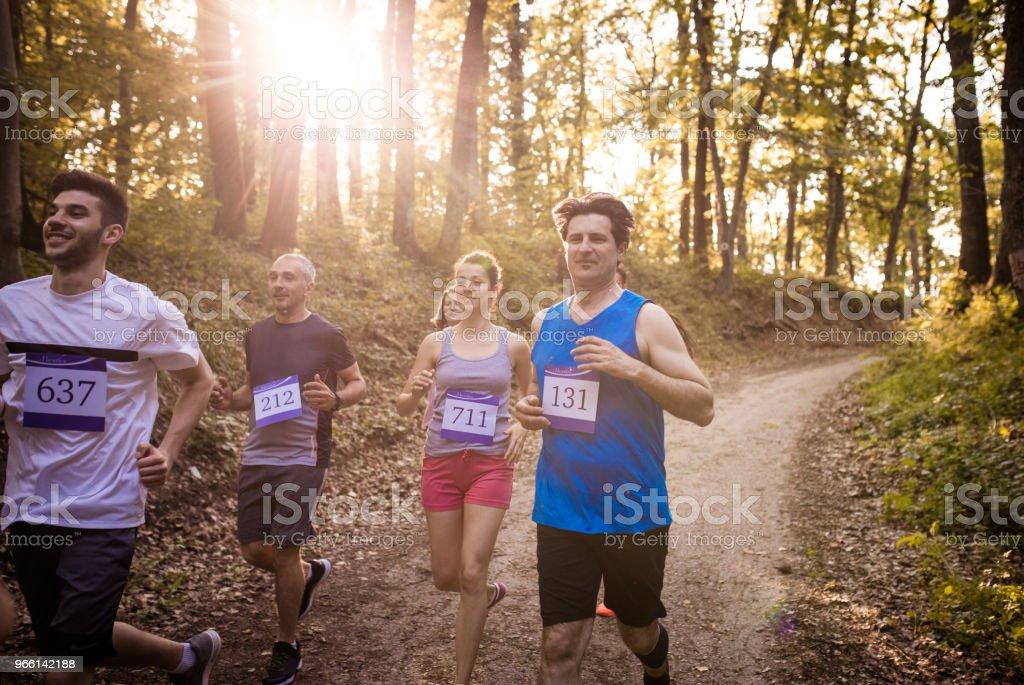Grupp av lycklig marathonlöpare racing i naturen - Royaltyfri Aktiv livsstil Bildbanksbilder