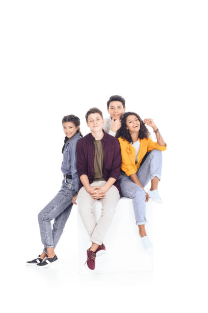 group of happy multiethnic students sitting on white cube isolated on white group of happy multiethnic students sitting on white cube isolated on white teenagers only stock pictures, royalty-free photos & images