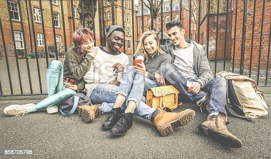 istock Group of happy multiracial best friends having fun using mobile smart phone - Young hipster people addicted by smartphone on social network community - Technology concept - Vivid saturated color tones 858705798