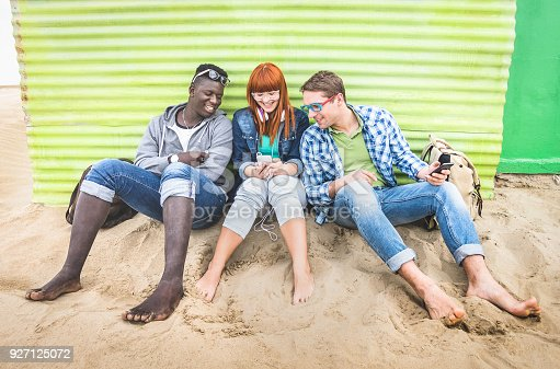 istock Group of happy multiracial friends having fun together using mobile smart phone - Young hipster people addicted by smartphone on social network community - Neutral cloudy filtered color tone 927125072