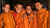 Group of happy Novice Buddhist monks in doors in the monastery in Bhaktapur, Nepal. Bhaktapur is an ancient town in the Kathmandu Valley and is listed as a World Heritage Site by UNESCO for its rich culture, temples, and wood, metal and stone artwork.