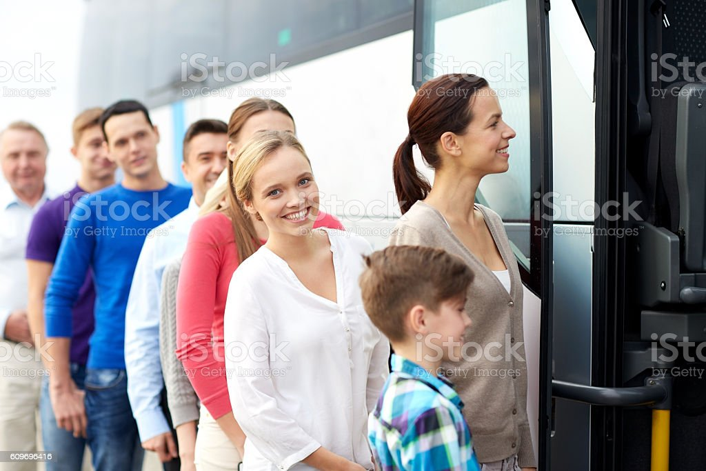group of happy passengers boarding travel bus stock photo