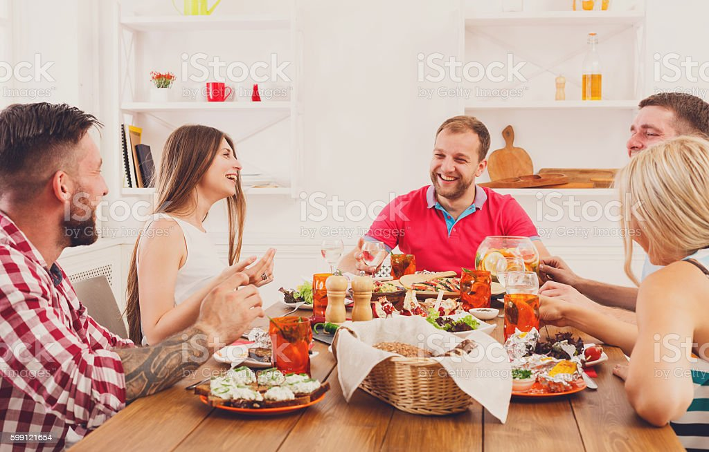 Group of happy people at festive table dinner party stock photo