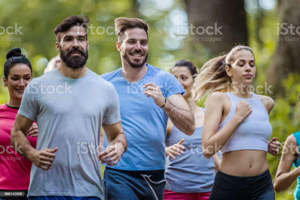 Group of happy people running a marathon race in nature. - Royalty-free Adult Stock Photo
