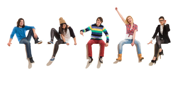 Young men and women sitting on a banner, smiling and gesturing. Full length studio shot isolated on white.