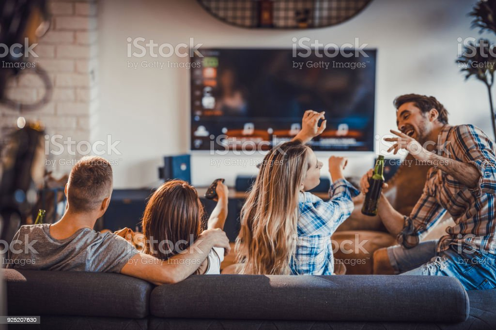 Group of happy people spending their time in the living room. stock photo