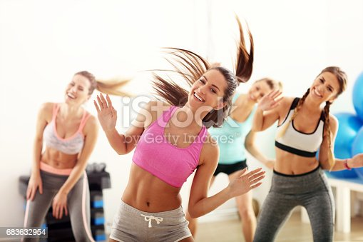 istock Group of happy people with coach dancing in gym 683632954