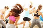 Group of energetic people with coach dancing in gym