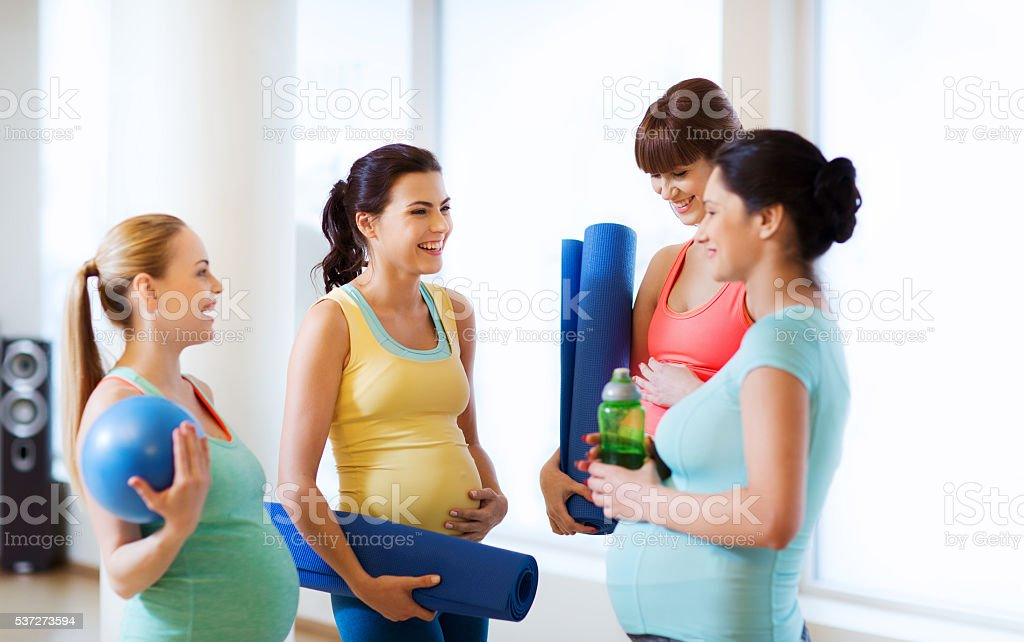 group of happy pregnant women talking in gym stock photo