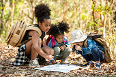 istock Group of happy pretty little girls hiking together with backpacks and sitting on forest dirt road with looking at the map for exploring the forest. Three kids having fun adventuring in sunny summer day 1211676347