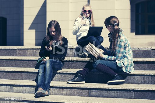 623358818 istock photo Group of happy school girls sitting on steps in campus 1162464714
