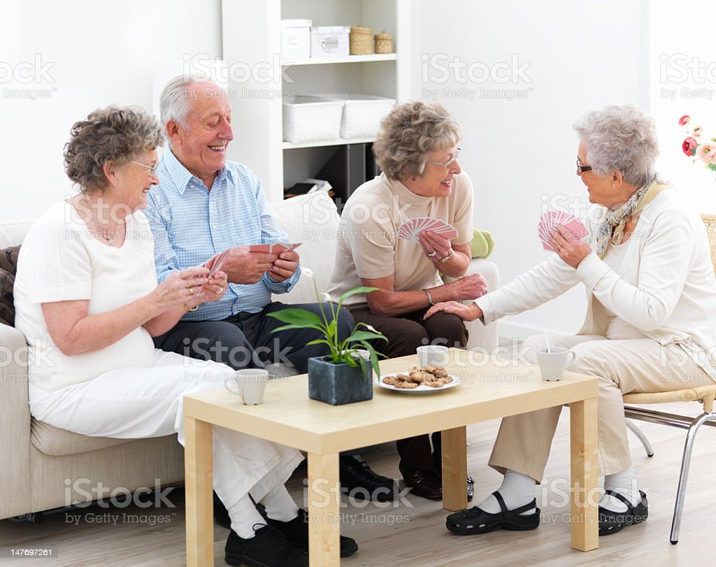 Group of happy senior men and women playing cards stock photo