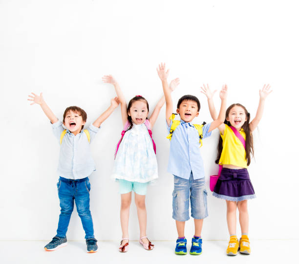 gruppe von glücklich lächelnde kinder heben die hände - taschen von liebeskind stock-fotos und bilder