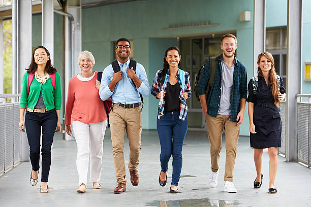 A group of happy teachers walking in a school corridor stock photo