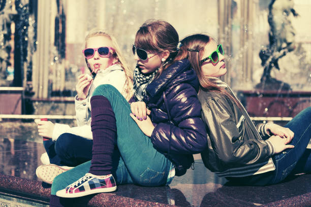 group of happy teen girls on city street - tween models stock photos and pictures