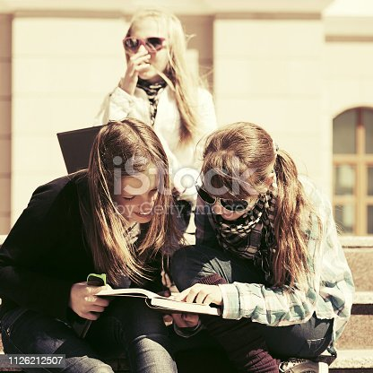 623358818 istock photo Group of happy teenage school girls reading a book in campus 1126212507